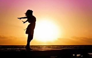 woman in sunset with arms outstretched