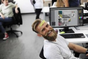 man laughing at workplace