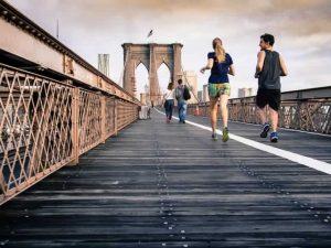 man and woman jogging over a bridge